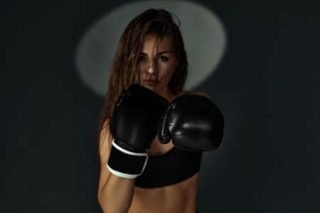 fashion photo of gorgeous sporty woman in boxing gloves punching on studio background. focus on glove