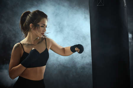 sporty brunette woman with boxing bandages in sportswear hitting the boxing bag on dark background with smoke.