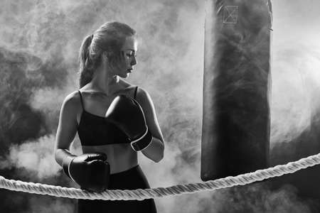 confident athletic brunette woman in boxing gloves and sportswear on ring. black and white Banco de Imagens