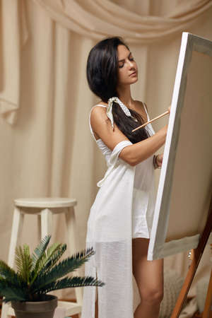 Young happy female artist in front of easel. Woman painting in art studio
