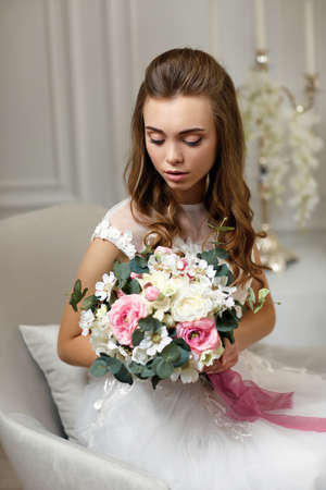 beautiful tender young bride with wedding makeup and long curly hair holding flower bouquet and sitting on armchair in white studio interior