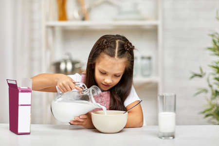 smiling cute little girl eating breakfast: cereal with the milk. child pours milk into a bowl of cereal in the kitchen. healthy breakfast