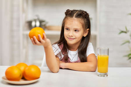 little child girl with oranges and juice in the kitchen. healthy food