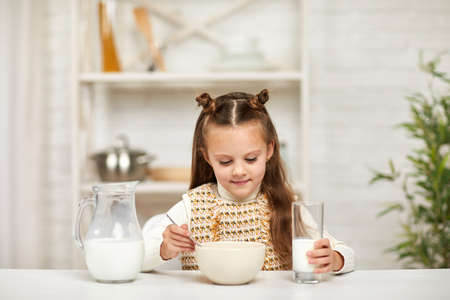cute little girl eating breakfast: cereal with the milk in the kitchen. healthy breakfast
