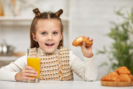 smiling little child girl having breakfast - fresh delicious croissants and orange juice in the kitchen.