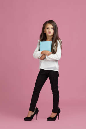 cute little child girl in oversized mothers shoes holding notebook on pink background. child playing businesswoman or teacher