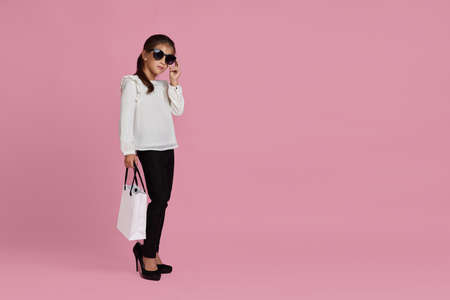 fashionable adorable little child girl in sunglasses and oversized mothers shoes is holding shopping bags on pink background. copy space for text. sale. black friday