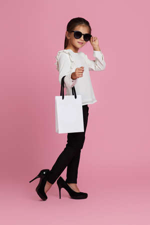 fashionable little child girl in sunglasses and oversized mothers shoes is holding white shopping bag on pink background.