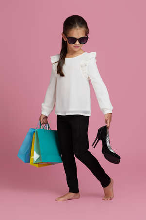 adorable little child girl in sunglasses is holding shopping bags and oversized mothers shoes on pink background. sale.