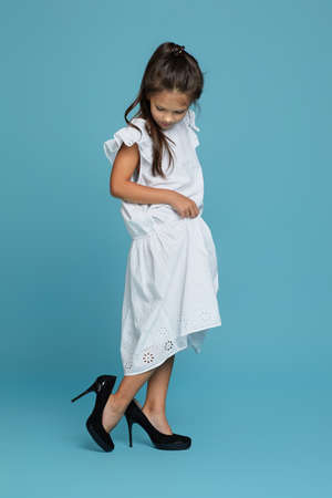 cute little child girl in white oversized dress and shoes on blue background. child playing grown ups