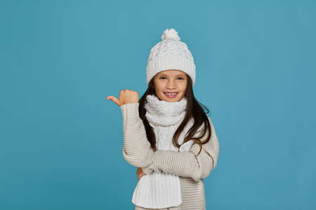 portrait of cheerful happy child girl in white winter knitted hat and sweater pointing to empty place on blue background. advertise here