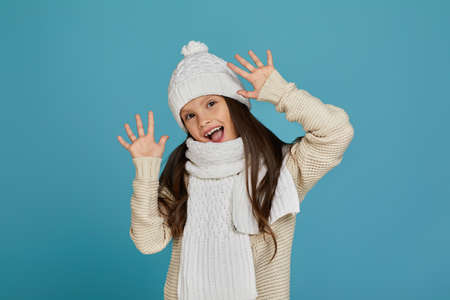 cheerful funny little child girl in white warm hat and scarf playing isolated on blue background Banco de Imagens