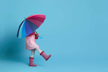 happy little child girl with multicolored umbrella in pink rain coat and rubber boots on blue background. space for text
