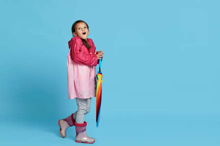 surprised cute child girl with multicolored umbrella in pink rain coat and rubber boots on blue background. Copy space for text