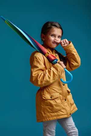 cute funny child girl with multicolored umbrella in yellow rain coat on blue background. autumn mood