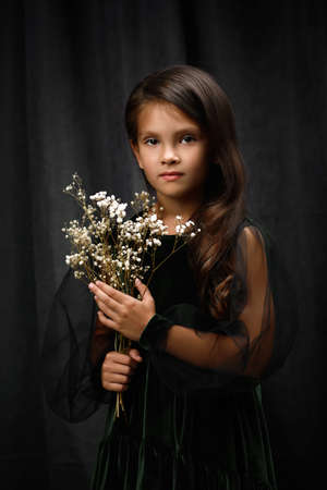 classical portrait of adorable little child girl in dark green dress is holding flowers Banco de Imagens