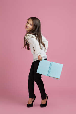 fashionable funny little child girl in oversized mothers shoes holding notebook on pink background. child playing businesswoman Banco de Imagens