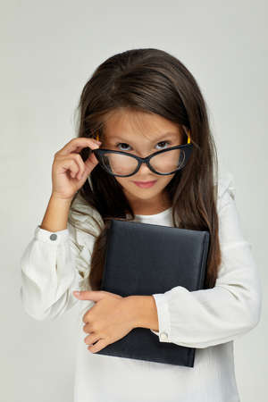cute little child girl in glasses holding notebook and looking at the camera on white background. Banco de Imagens
