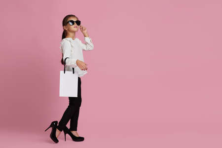 Sale. fashionable cute little child girl in sunglasses and oversized mothers shoes is holding white shopping bag on pink background. copy space for text Banco de Imagens
