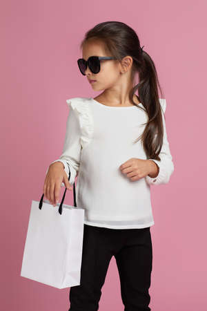Sale. cute fashionable elegant little child girl in sunglasses is holding shopping bag on pink background. Banco de Imagens