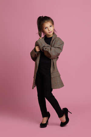 cute little child girl in white oversized mothers jacket and shoes on pink background. child playing adult life