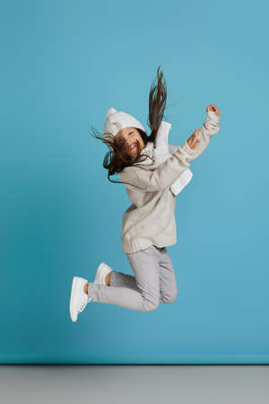 Excited smiling cheerful little child girl in white winter knitted hat and sweater jumping on blue background