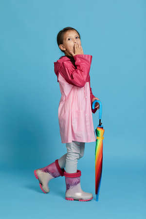 surprised cute child girl with multicolored umbrella in pink rain coat and rubber boots on blue background. Banco de Imagens