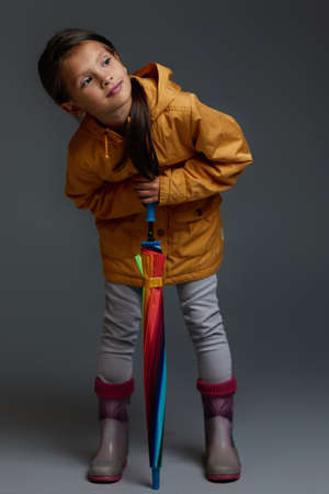 Cheerful child girl with multicolored umbrella in yellow rain coat and rubber boots on gray background.
