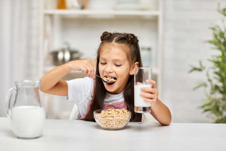 smiling cute little girl eating breakfast: cereal with the milk in the kitchen. healthy breakfast