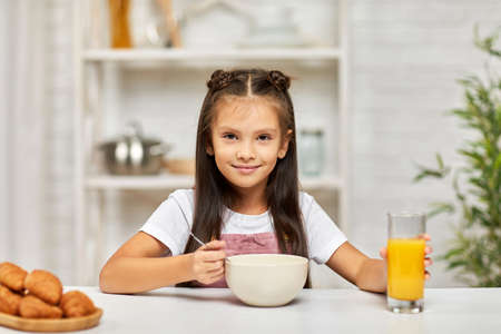 cute little child girl having breakfast - cereal and orange juice in the kitchen. healthy breakfast