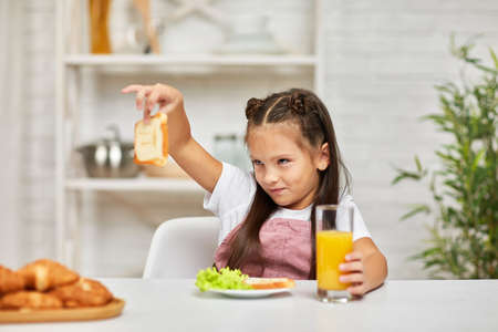 the child does not want to have breakfast. little girl looks at the sandwich with disgust Banco de Imagens