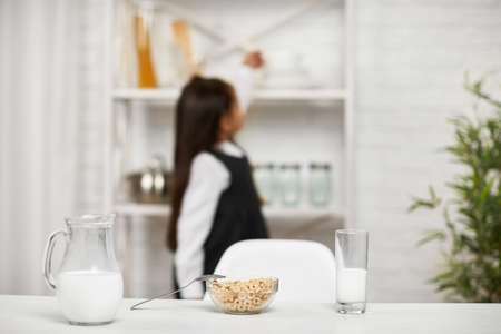breakfast with cereal with the milk in the morning in kitchen. child near the shelf in the background