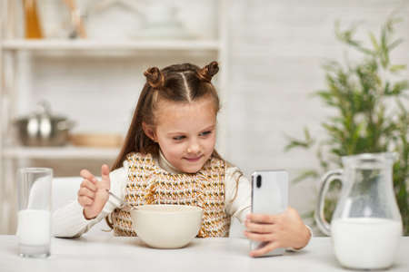 cute little girl eating breakfast: cereal with the milk and looking cartoon in smartphone in the kitchen. healthy breakfast Banco de Imagens