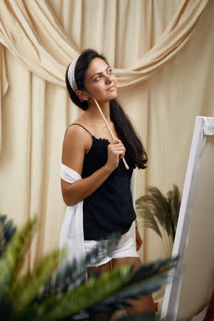 attractive thoughtful female artist in front of easel. Woman painting in art studio with plants.