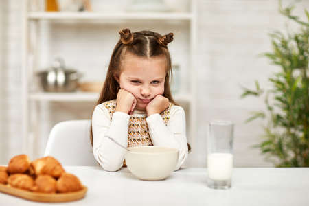 the child does not want to have breakfast. little girl looks at the cereal with the milk with disgust Standard-Bild
