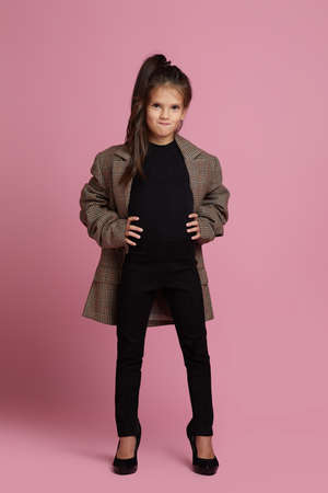 cute little child girl in white oversized mothers jacket and shoes on pink background. child playing businesswoman