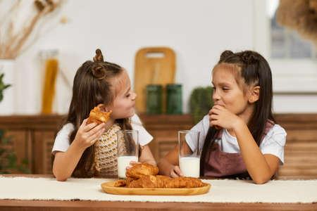 funny cute little children girls having breakfast - fresh delicious croissants and milk in the kitchen.