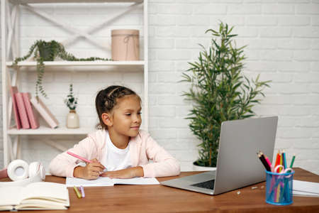 happy little child girl using laptop for studying online learning system. online lesson at home