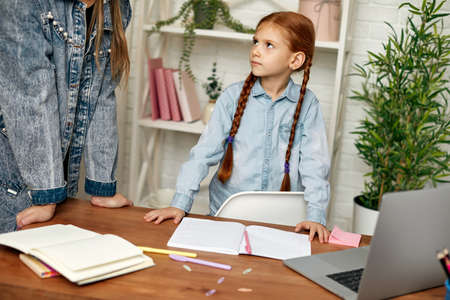 little child girl child does not want to study online. mom makes daughter learn lessons. hard online lesson at home Stockfoto