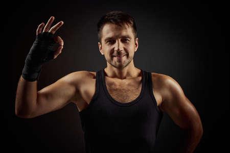 Handsome fit smiling bearded man showing Ok gesture on black background