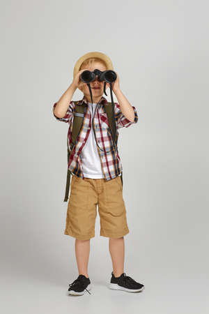 Little boy tourist with backpack looking through a binoculars. Little boy scout dreams of traveling