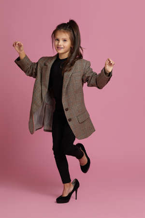 funny little child girl in white oversized mothers jacket and shoes on pink background. child playing grown ups