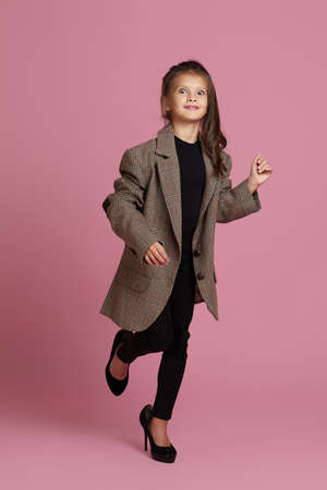 happy little child girl in white oversized mothers jacket and shoes on pink background. child playing grown ups