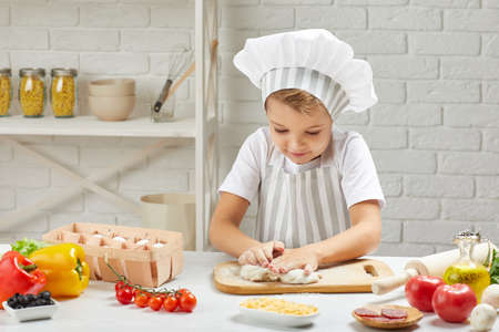 little child boy in chef hat and an apron knead the dough in the kitchen 版權商用圖片