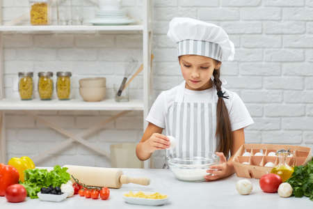 cute little girl in chef hat and an apron is breaking yellow egg into fresh dough in the kitchen. child cooking with dough