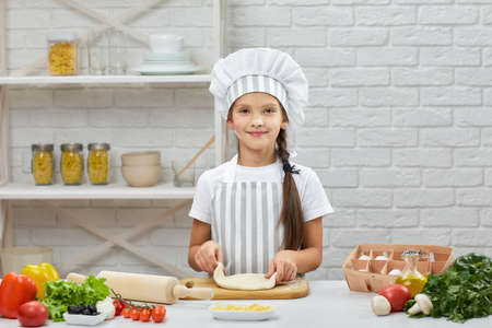 smiling little child girl in cap and an apron knead the dough in the kitchen