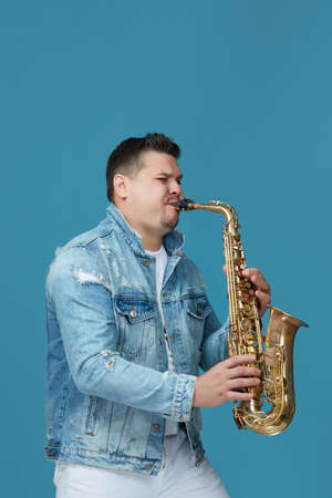 handsome musician playing the saxophone in the studio blue background. Music concept.