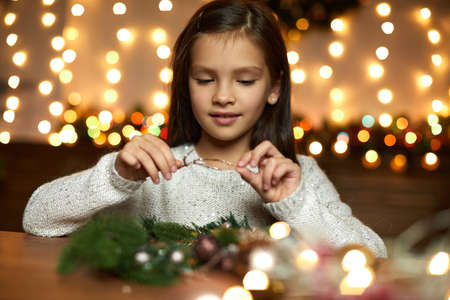 happy cute little child girl makes a handmade Christmas wreath at home.