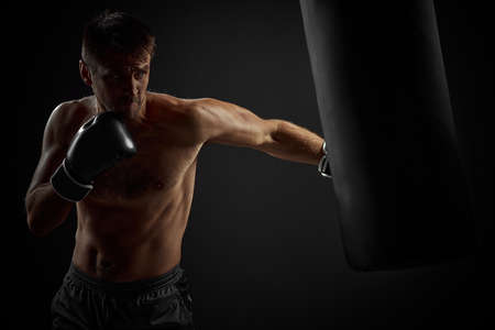 muscular boxer in black boxing gloves punching in boxing bag on dark background Stock Photo