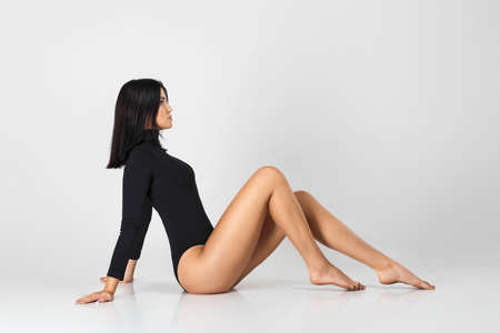 Fit beautiful woman with perfect body and legs in black bodysuit posing over studio background. Slim body shape, fitness and diet concept. Foto de archivo